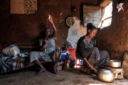 A woman member of the Ethiopian Jewish community works with a wool spool while another cooks at their home in the city of Gondar, Ethiopia