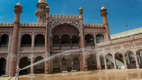 A worker disinfects a mosque during the Islamic holy month of Ramadan, in Peshawar