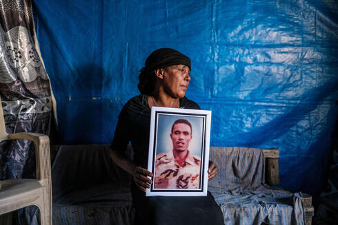 Azanu Girmay holds a portrait of her deceased son at her house in Gondar, Ethiopia