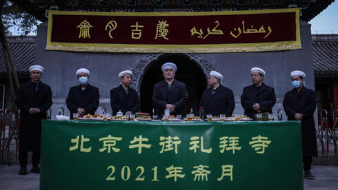 Muslim people pray before eat as they break fast with other devotees on the first day of the fasting month of Ramadan at the Niujie Mosque in Beijing city, China