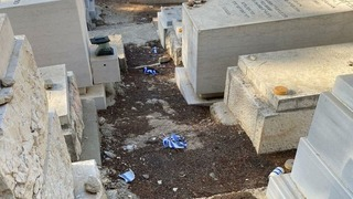 Torn up Israeli flags near gravestones at Har HaMenuchot Cemetery