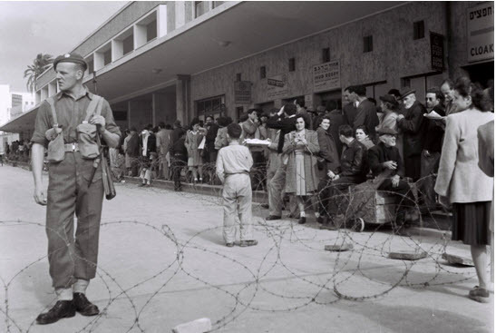 A British soldier guarding the fenced off Tel Aviv central bus station during a curfew imposed under martial law in 1947