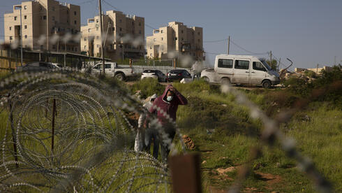 Palestinian laborers head home after their work day on construction projects in the West Bank Jewish settlement of Efrat