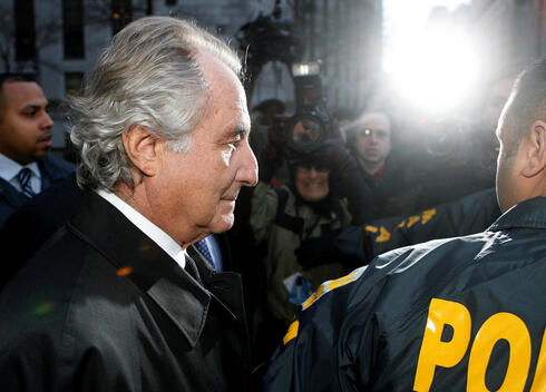 Disgraced financier Bernard Madoff is escorted by police and photographed by the media as he departs U.S. Federal Court after a hearing in New York, January 5, 2009