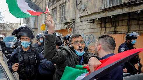 Palestinian demonstrator is pushed by an Israeli policeman during a protest against visits by Israeli settlers, in Hebron