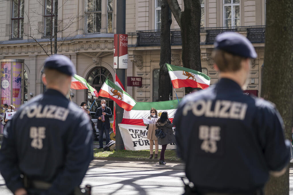 Protesters carrying the flag of an Iranian opposition group stand opposite police officers near the Vienna hotel as the nuclear talks with Iran were taking place last month