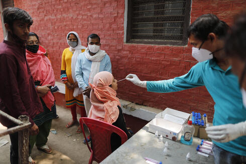 A health worker takes a swab sample to test for COVID-19 in the northern Indian city of Prayagraj, April 17, 2021