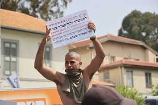 A man protests in Tel Aviv over the poor treatment of wounded IDF veterans. One of the slogans on the banner reads: 'No man left behind'