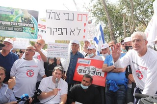 IDF Disabled Veterans Organization Chairman Idan Kliman (sitting, holding microphone) speaks at protest of alleged government neglect of soldiers and veterans in Tel Aviv