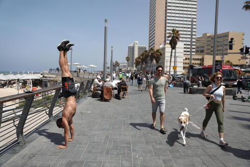 Israelis without face masks enjoy the spring sunshine in Tel Aviv on Saturday, a day before the mask mandate was officially lifted