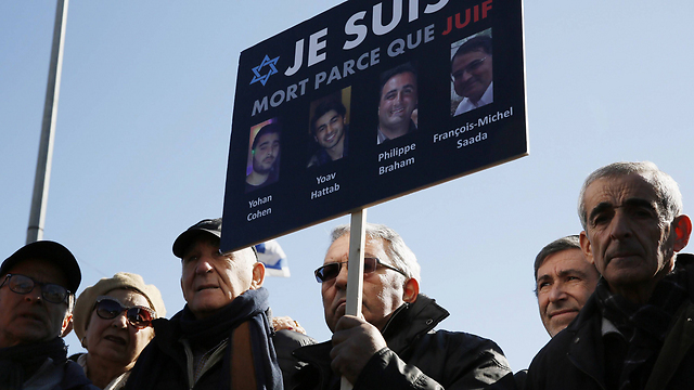Mourners hold up images of the four victims of a deadly attack at a Paris kosher supermarket during their funerals in Jerusalem in January 2015