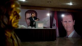 Syrian election official waits for voters at a polling station with posters of President Bashar Assad during the parliamentary election in Damascus, Syria, April 13, 2016