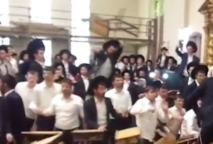 A chair flies during clashes at the yeshiva