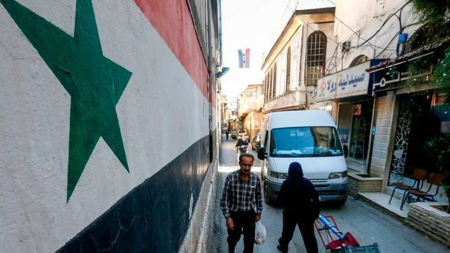 Man walks past mural of Syrian flag in Damascus