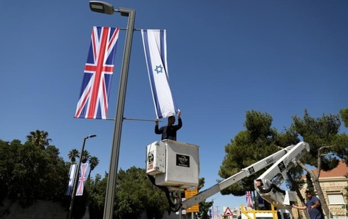 A Jerusalem municipality worker hangs an Israeli flag next to the British flag, the Union Jack, as he stands on a platform near Israel's presidential residence in Jerusalem ahead of the upcoming visit of Britain's Prince William, June 25, 2018