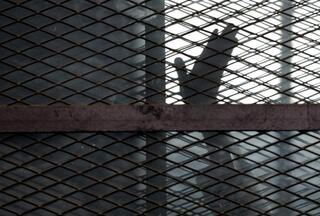 A member of the Muslim Brotherhood waves his hand from a defendants cage in a courtroom in Torah prison in Cairo