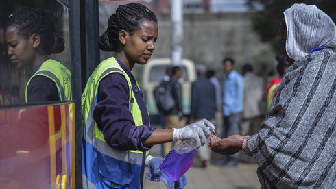 A volunteer provides hand sanitizer to passengers entering a bus as a precaution against the spread of the new coronavirus in the capital Addis Ababa, Ethiopia