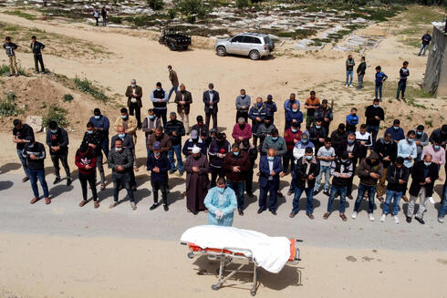 A picture taken with a drone shows Palestinians praying next to the body of a man, who died after contracting the coronavirus disease (COVID-19), before burial at a cemetery in the central Gaza Strip