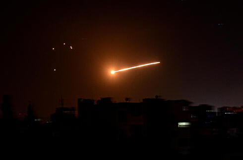 A streak of light is seen in the night sky in the vicinity of the Syrian capital Damascus during what Syrian authorities said was an Israeli air strike