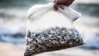 Julian Melcer collects cigarette butts from the shore of the Mediterranean Sea as part of his environmental campaign, at a beach in Tel Aviv