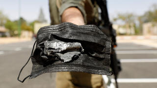 Soldier holds shrapnel from the Syrian missile