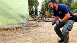 A security officer inspects the damage after a rocket strike at a community close to the Gaza border overnight Friday