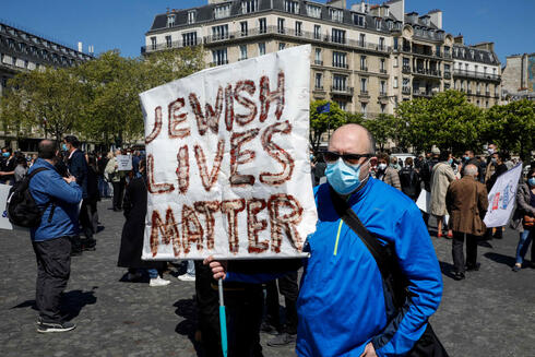 A man holds a placard reading 'Jewish Lives Matter' at a Paris protest Sunday over the decision not to try the killer of a French Jewish woman