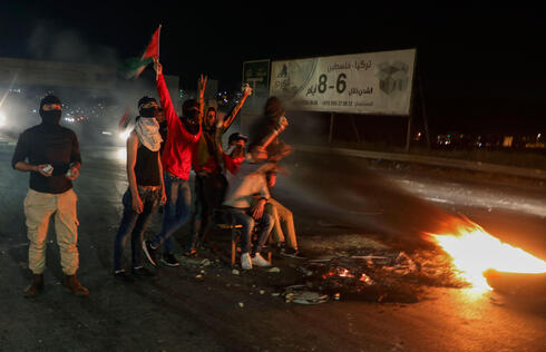 Palestinian protesters gesture next to burning tires during clashes with Israeli security forces at the Hawara checkpoint in the West Bank on Saturday night
