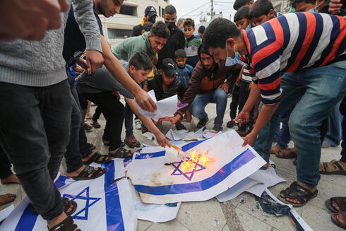 Palestinians in Gaza burn Israeli flags during a protest Saturday over tensions in Jerusalem