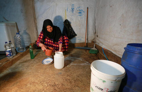 Um Ahmad, Hussein al-Khaled's wife, washes dishes inside a tent at an informal tented settlement in Bar Elias, in the Bekaa Valley, Lebanon April 22, 2021