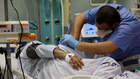 nurse monitors the health of a COVID-19 patient at the coronavirus intensive care unit, at the Turkish-Palestinian Friendship Hospital in Gaza