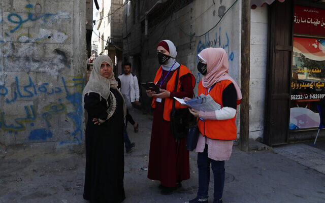 Members of the Central Elections Commission's field team checks to register a local woman to the electoral roll, at the main road of Gaza City