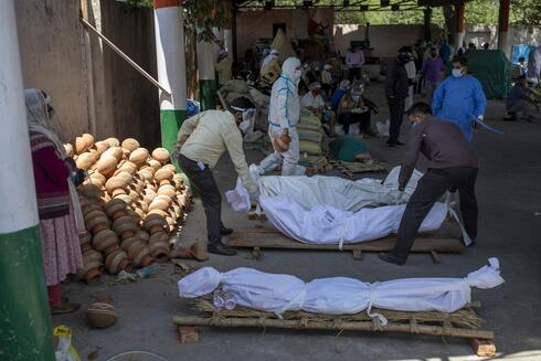 People line up dead bodies of those who died of COVID-19 at a crematorium, in New Delhi, India