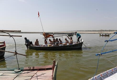Hindus arrive to immerse the ashes of their relative who died of COVID-19 at the confluence of rivers Ganges and Yamuna, sacred to them, in Prayagraj, India