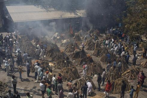 Multiple funeral pyres of those who died of COVID-19 burn at a ground that has been converted into a crematorium for the mass cremation of coronavirus victims, in New Delhi, India