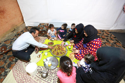 Hussein al-Khaled and his family eat their Iftar (breaking fast) meal during the holy month of Ramadan inside a tent at an informal tented settlement in Bar Elias, in the Bekaa Valley, Lebanon April 22, 2021