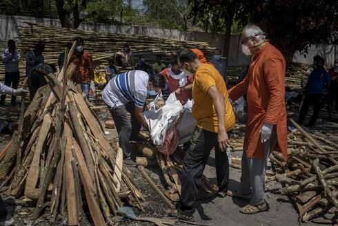 Family members put the body of their relative, who died of COVID-19 on the funeral pyre at a crematorium in New Delhi, India