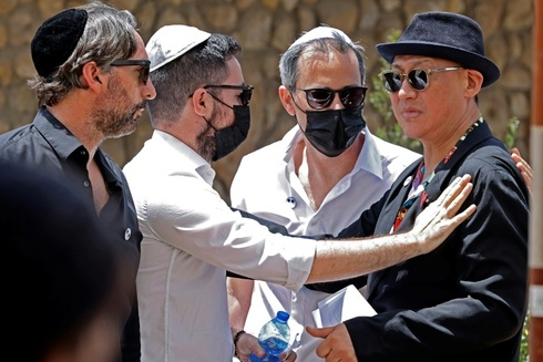 Alber Elbaz's relatives with his long-term partner at his funeral in Holon on Wednesday