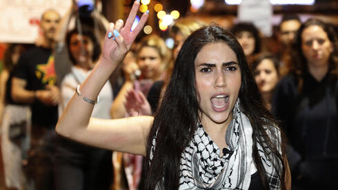 An Arab woman shouts slogans against Jewish nationalist religious groups that are buying up property in the Arab neighborhood of Jaffa, in Tel Aviv, Israel, Saturday, April 24, 2021