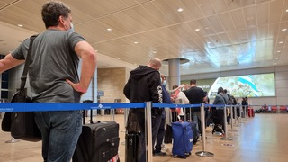 People line up to board their flight at Ben Gurion Airport