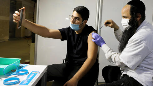 A man receives a vaccination against the coronavirus disease (COVID-19) at a temporary Clalit healthcare maintenance organisation (HMO) vaccination centre, at a sports arena in Jerusalem