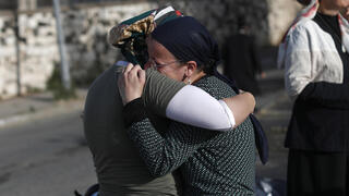 Family members mourning the loss of a loved one in the Meron stampede