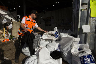 An official collects the personal belongings of the victims of the Meron disaster