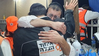 Rescue workers embrace after 45 people died in a stampede on Mount Meron in April