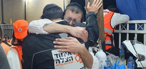 Emotional rescue workers share a hug at the scene of the Meron disaster on Thursday night