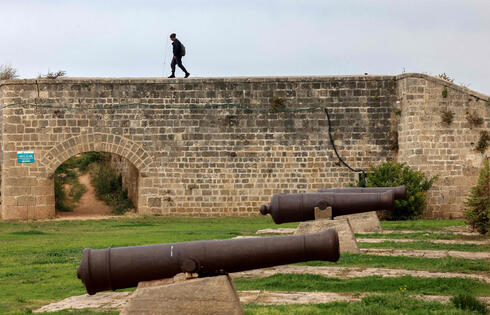 A man walks along the city walls of the old town Acre where  Napoleon Bonaparte and approximately 13,000 French soldiers started an unsuccessful siege of the Ottoman-controlled city on March 20, 1799