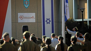 Israeli soldiers stand in formation as the national flag is lowered to half-mast as the country observes a day of mourning