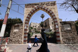 A woman and a child walk past Qasr al-Basha in Gaza City
