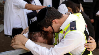 Emergency workers embrace in tears after the disaster at Meron