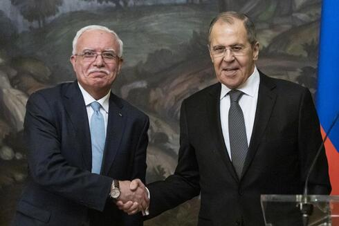 Russian Foreign Minister Sergey Lavrov, right, and Palestinian Foreign Minister Riyad Al-Maliki shake hands as they leave a joint news conference following their talks in Moscow, Russia